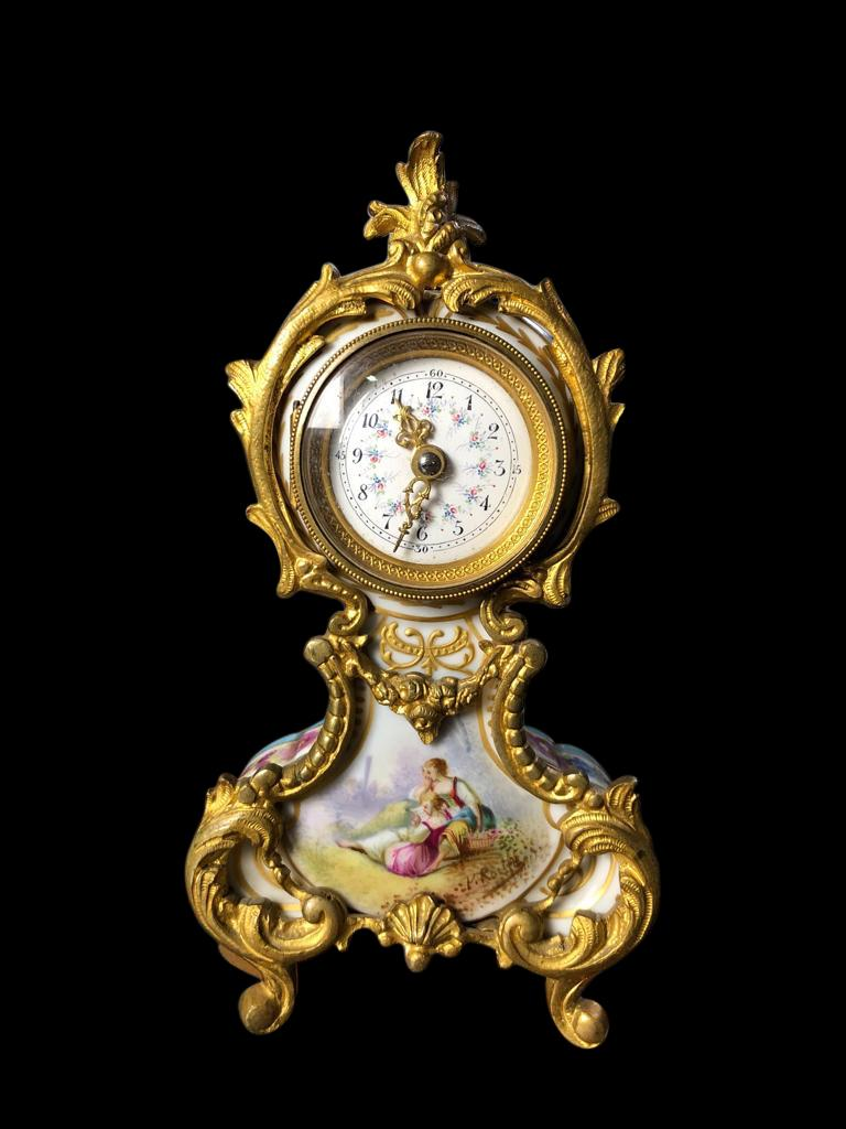 A spectacular Meissen mantel (fireplace) table clock, 19th century. The clock is offered in great original condition, with a stunning gold gilded frame, and hand painted scenes of a couple on the front followed with floral decoration on back and