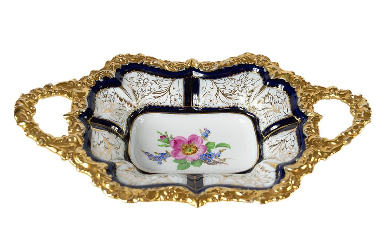 Meissen Porcelain deep cabinet plate with handles. This piece is hand painted in cobalt blue with floral motive in the center and richly decorated gold edge.