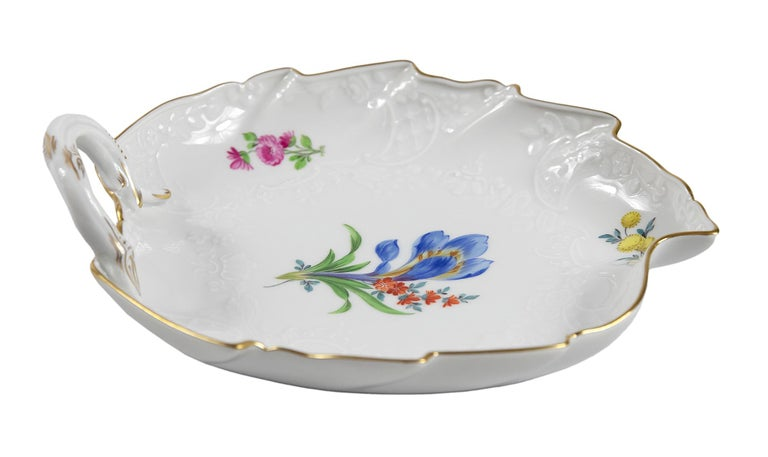 Meissen Porcelain leaf form plate with handle. This piece is hand painted with floral motives and decorated with gold on edge and handle. Signed on the bottom.