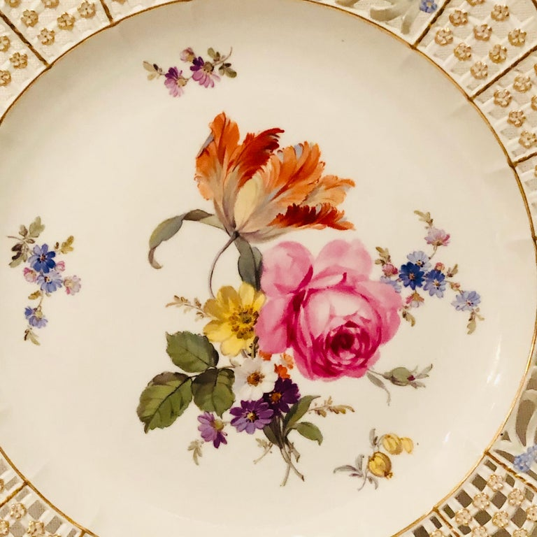 This is an exquisite Meissen cabinet plate painted with a large beautiful flower bouquet with a large tulip and other flowers. The Meissen plate has a very intricate reticulated or open work border profusely decorated with raised gold and blue
