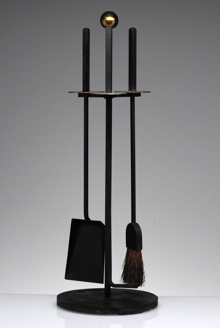 Cast iron and brass Mid-Century Modern design by Mel Bogart for Stewart-Winthrop. Set includes hearth broom, poker, shovel and stand. Good Design paper label to underside.
