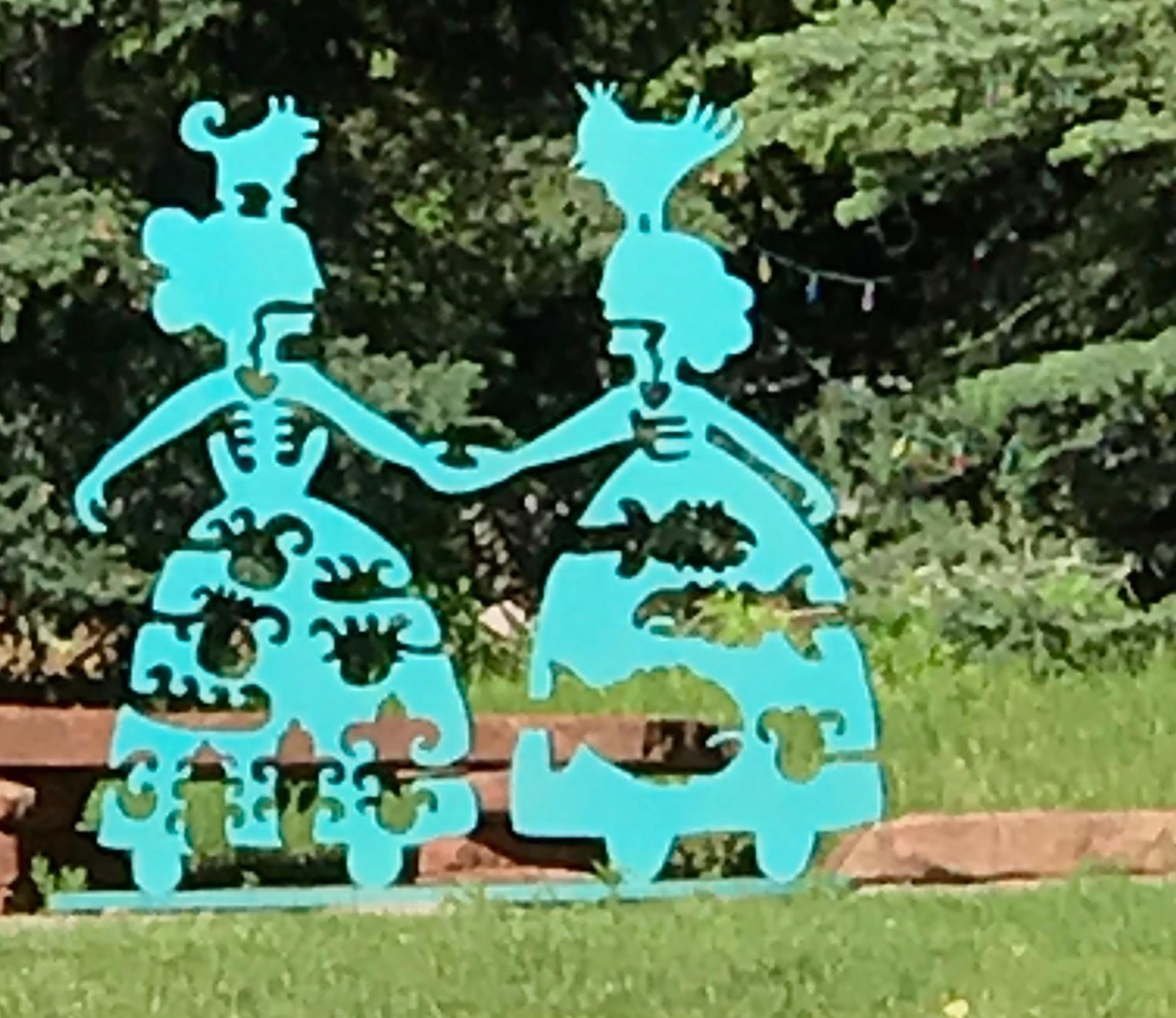 Making New Friends, teal aluminum sculpture Korean & Navajo Women outdoor heart