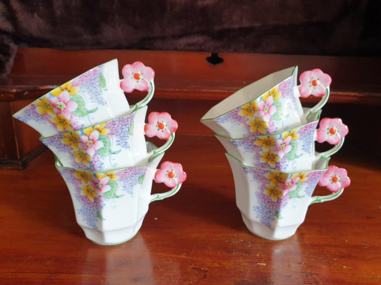 Melba pink flower handle tea service patten number 3787, Lilac time from the Art Deco period. This set comprises 6 hexagonal shaped cups and saucers, 6 cakeplates, sugar bowl and creamer and 1 large cakeplate. All in perfect condition. Each piece is