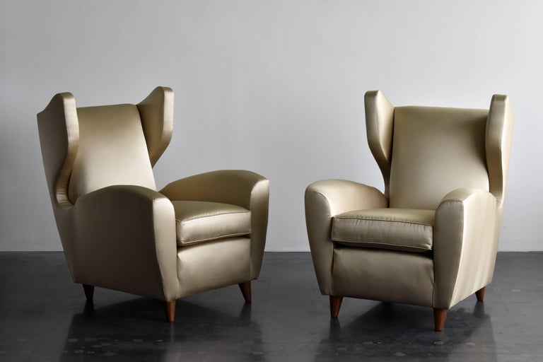 A pair of organic lounge / wingback / high back chairs designed and produced by Italian architect Melchiorre Bega. wooden legs, upholstered in brand new light gold / bronze metallic satin fabric.   Melchiorre Bega is considered one of Italy's most