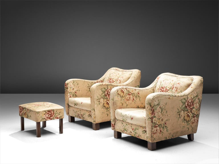 Melchiorre Bega, armchairs and ottoman, Italy, circa 1935   This pair of padded armchairs come with a footrest of a square design. The set features parallelepiped front legs and back legs in solid oak, and the seat and back is covered in a flower