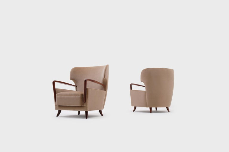 Rare set of wingback armchairs by Melchiorre Bega (1898-1976), Italy, 1950s. Stunning and exceptional design from the highest quality. The sharp wingback and organically carved armrests and feet out of solid mahogany are the signature of this