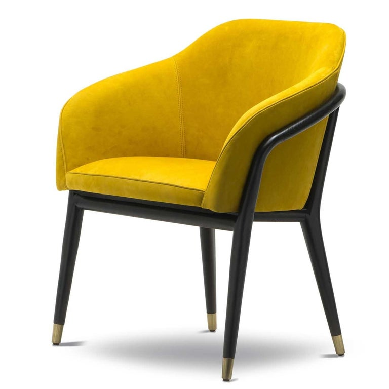 A dash of vibrant color and a midcentury inspiration are the distinctive qualities of this exquisite chair that will enliven a modern entryway, living room, or private study. The base in solid cinder-colored ash has metal tips with a satin brass