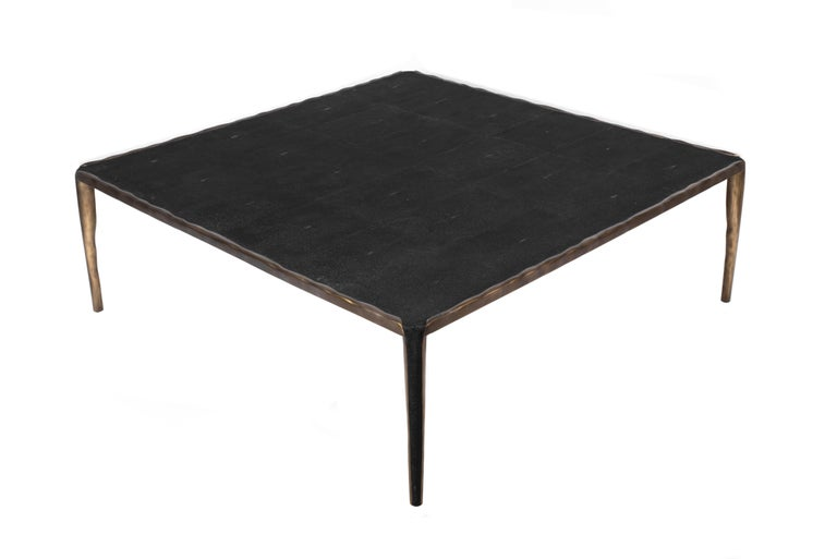 The melting coffee table is inlaid in black shagreen and the top is framed with the an irregular surface bronze-patina brass that continues onto the legs, which creates the