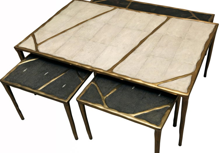 The melting nesting coffee tables are sold as a set of 4, the large is inlaid in cream shagreen, the medium in black pen shell, and the two small sizes in black shagreen. These pieces have a bronze-patina brass pattern that