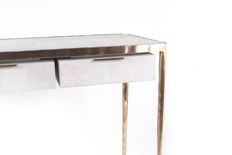 The melting writing desk's simple but elegant design, makes for an adaptable neutral piece of furniture. The cream shagreen top is framed with an irregular surface bronze-patina brass that creates the