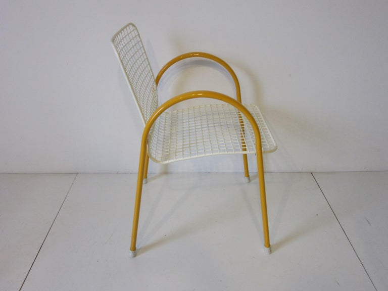 A set of four white wire seated chairs with yellow one piece arching arms and legs with rubber end caps for feet. These chair stack nicely and have a coated finish for protection, retains the manufactures label made in Italy by the EMU furniture