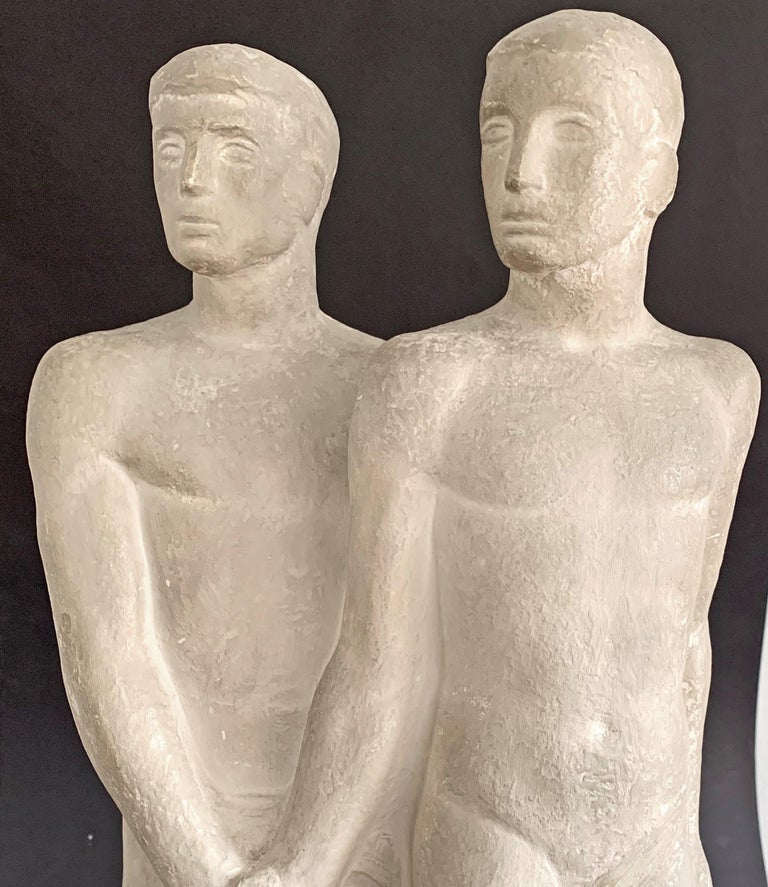 Beautiful and dignified, this remarkable and powerful sculpture depicts a nude male couple clasping hands, either in solidarity, collegiality or intimacy -- it is difficult to be certain. Given that the reverse of the sculpture shows one figure