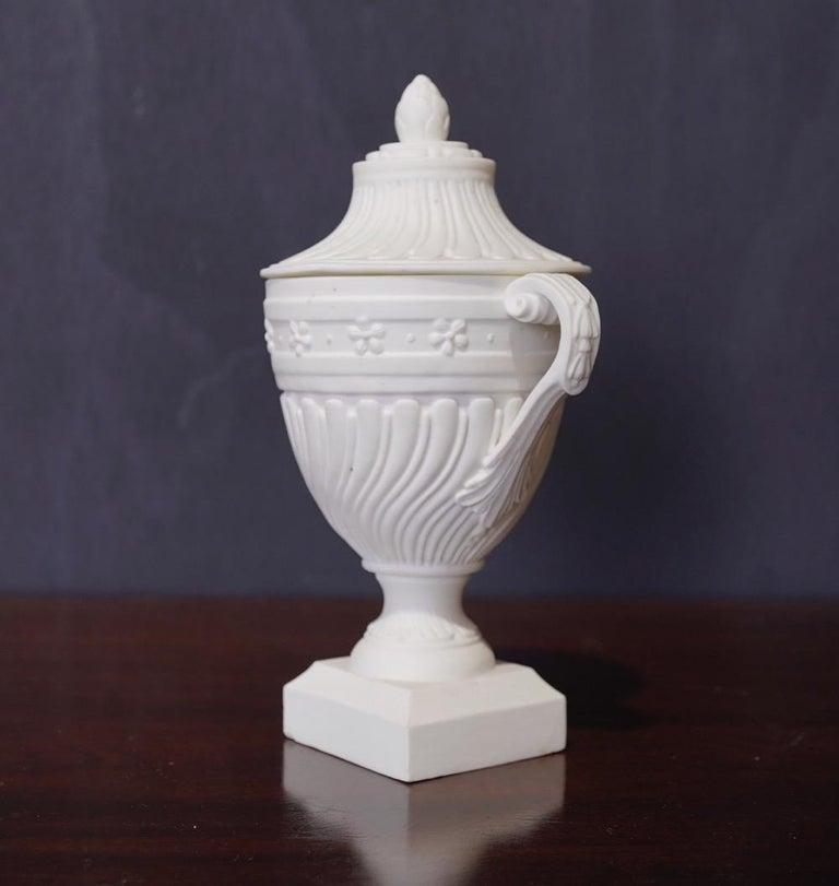 Rare Mennecy unglazed porcelain classical covered urn, with spiral fluted body and lid, twin scroll handles to the sides, the knop modelled as an artichoke, on a square plinth base. Inscribed mark DV,, f  circa 1765.