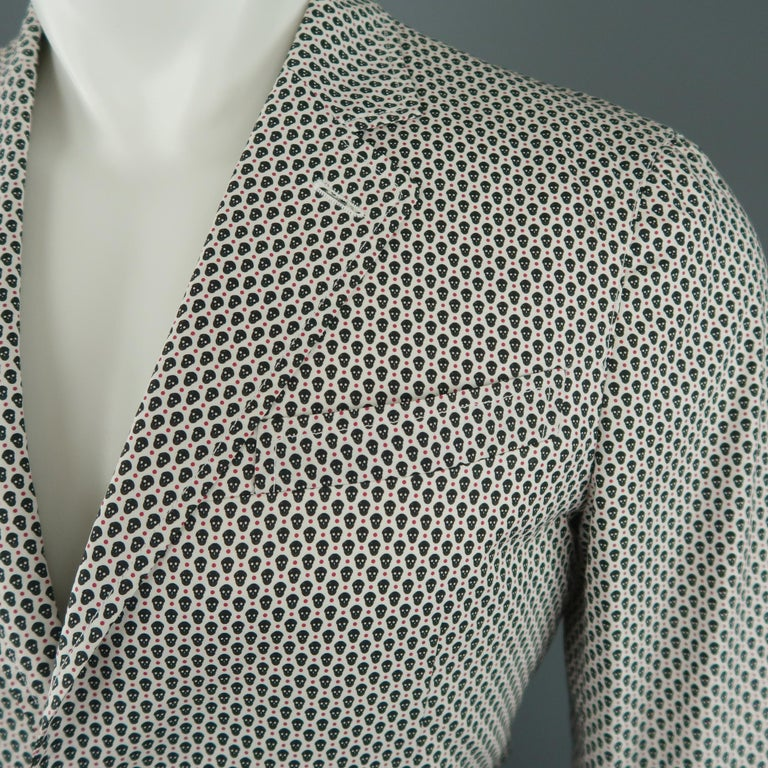 ALEXANDER MCQUEEN sport coat comes in white cotton with all over black and red spotted skull print, notch lapel, single breasted, two button closure, and single vented back. Made in Italy.   New with Tags. Retails: $1,155.00. Marked: IT 44