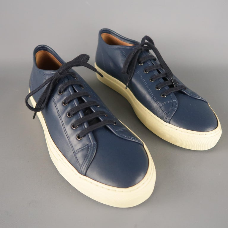 COMMON PROJECTS Achilles are navy solid leather low-top sneakers, accented with a gold metallic