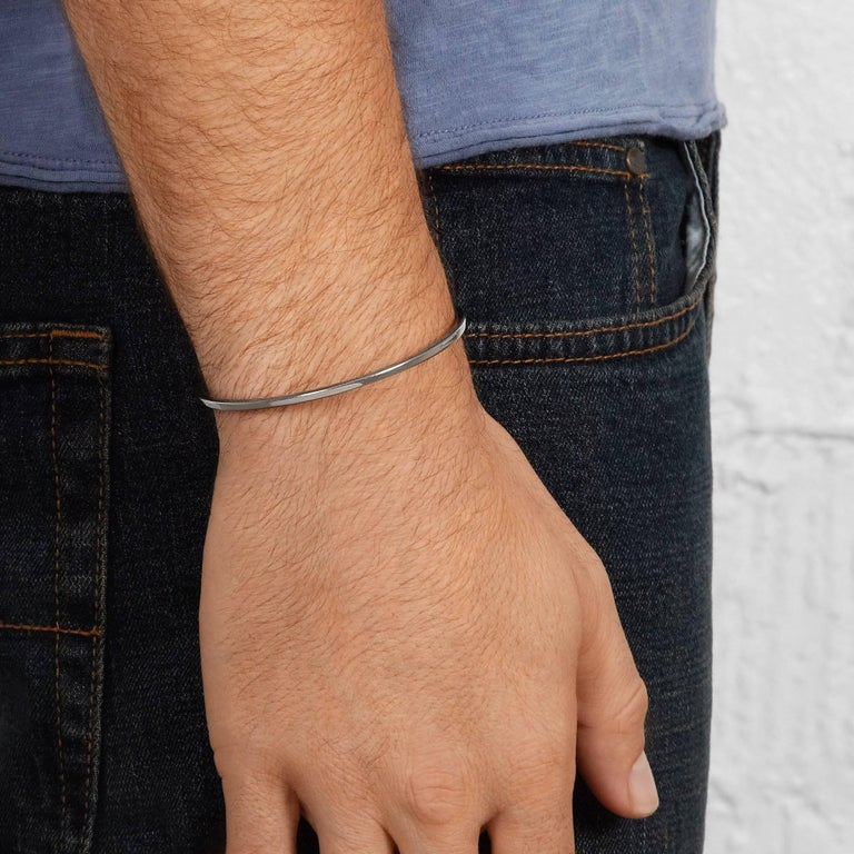 This simple men's cuff bracelet is crafted in oxidised sterling silver and accented with solid 18-carat yellow gold cubes at each end.   Handmade in London. Hallmarked 925 Allison Bryan London.