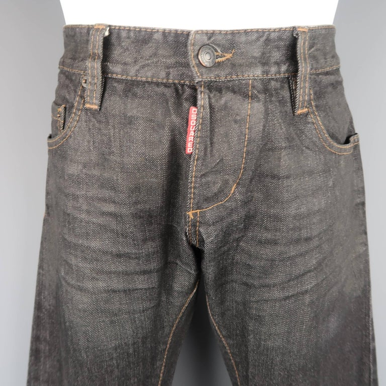 DSQUARED2 jeans come in charcoal raw selvedge denim with a red logo tab fly, distressed wax coated effect top, and permanent cuffed hem. Made in Italy.   Good Pre-Owned Condition. Marked: IT 48   Measurements:   Waist: 34 in. Rise: 8.5 in. Inseam: