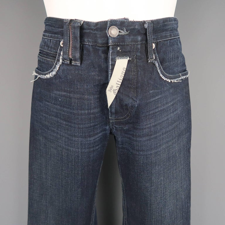 JOHN GALLIANO jeans come in navy washed denim with distressed trim, zipper belt loop, logo ribbon fly embellishment, and metal hoop detailed back. Made in Italy.   Good Pre-Owned Condition. Marked: IT 46   Measurements:   Waist: 30 n. Rise: 9.5