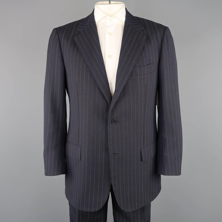 Vintage KITON for WILKES BASHFORD suit comes in navy blue pinstripe wool and includes a single breasted, three button, notch lapel sport coat and matching flat front trousers. Made in Italy.   Good Pre-Owned Condition. Marked: IT 54   Measurements: