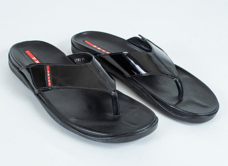 The ultimate in casual luxury, these sandals offer a padded comfort footbed and a non-slip textured rubber sole for safety. Their mirror-shine patent leather strap and iconic red logo impart unexpected style in a small package.  Black patent leather