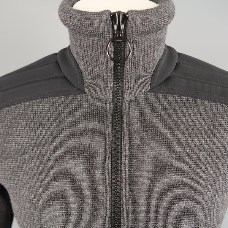 PRADA jacket comes in gray wool knit with a high collar, double zip front, and padded nylon moto detailed sleeves. Hole on back. As-is.   Good Pre-Owned Condition. Marked: IT 48   Measurements:   Shoulder: 16 in. Chest: 39 in. Sleeve: 25 in. Length: