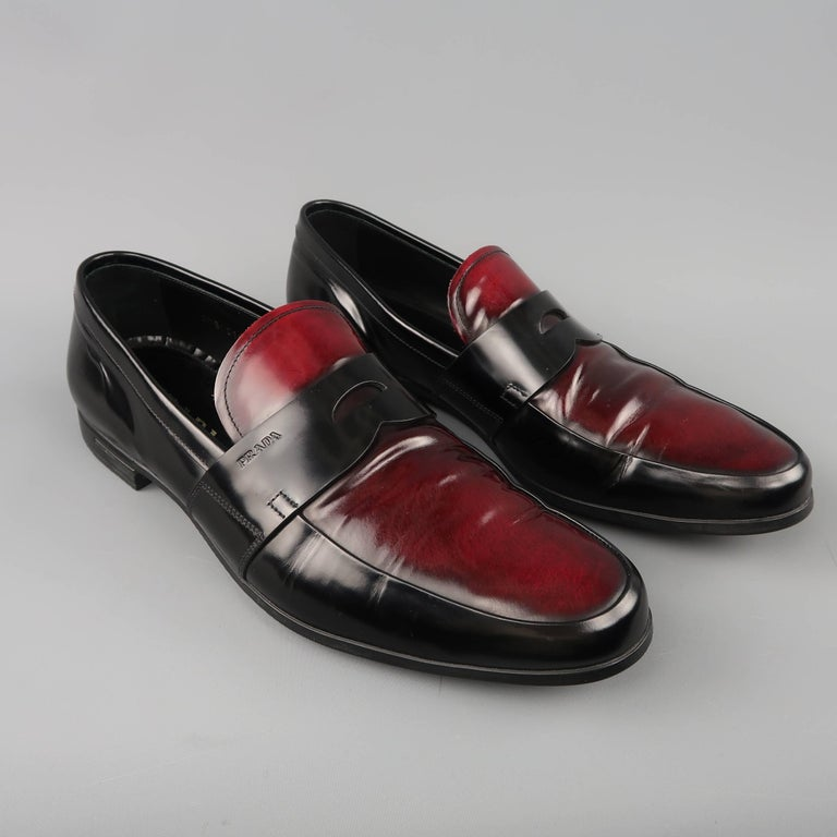 6f7b1712899 PRADA penny loafers come in black glossy leather with antiqued burgundy  leather panels and penny strap