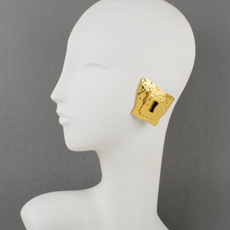 Very chic Mercedes Robirosa Paris clip-on earrings. Oversized modernist style with dimensional geometric shape featuring a sort of lock entry with gilt metal all textured and lightly hammered. Signed at the back with brand logo. Measurements: 1.75