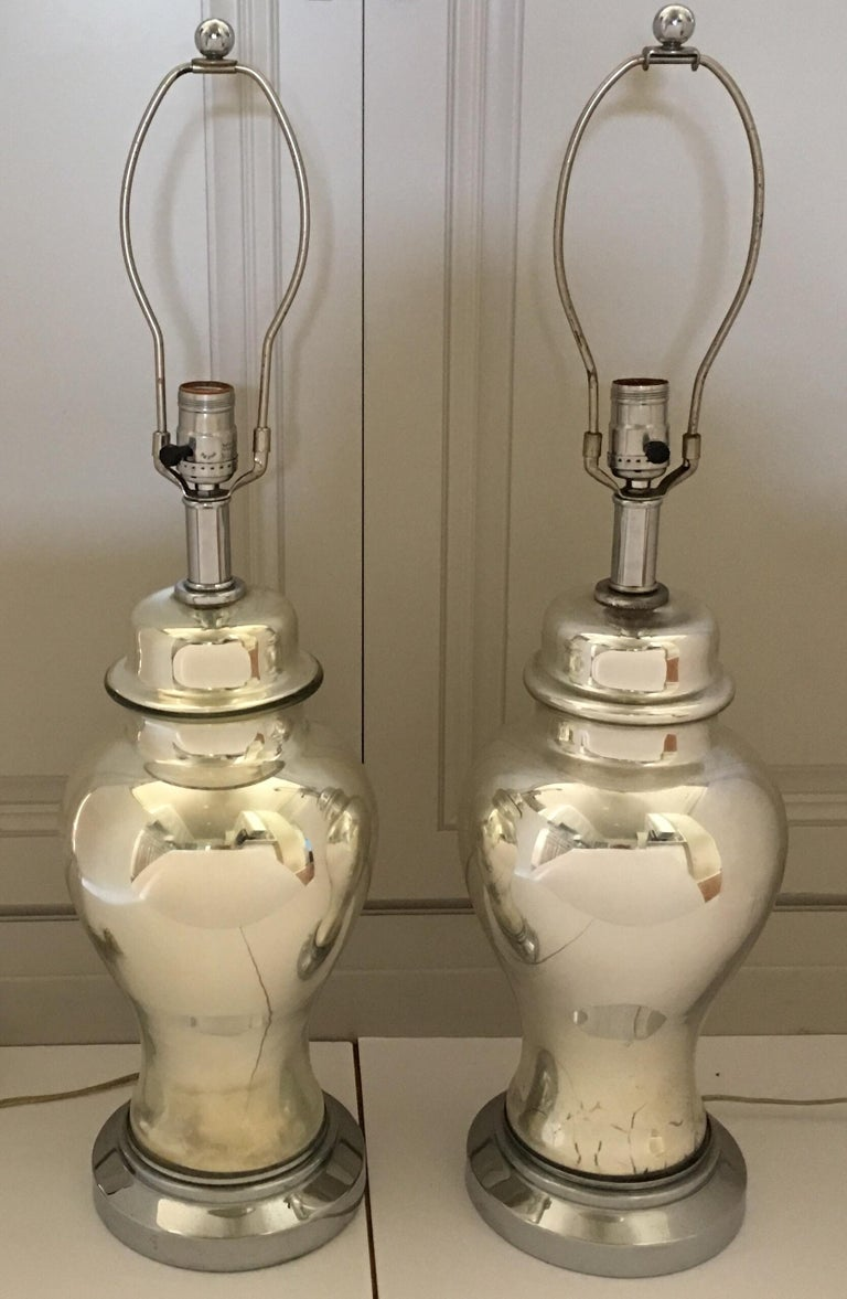 Pair of midcentury mercury glass ginger jar table lamps. These reflective mirror-like lamps are mounted on round nickel plated plinth bases. Beautiful bedside or living room lamps. Lamp shades not included.  28 inches high to finial. 21 inches