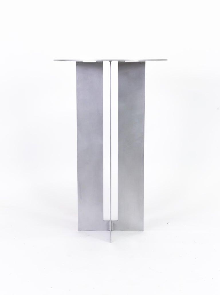The Mers cafe table is fabricated from solid aluminum. It is suitable for use indoors and out.  Shown in aluminum with satin finish. Custom sizing and powdercoat color available.  Overall dimensions: 26