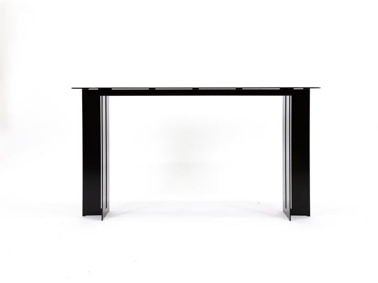 The Mers console table is fabricated from solid aluminum and is suitable for use indoors and out. Form is inspired by the simple utilitarianism of West Coast aluminum fishing boats.  Shown in aluminum with Black powdercoat finish.  Custom sizing and