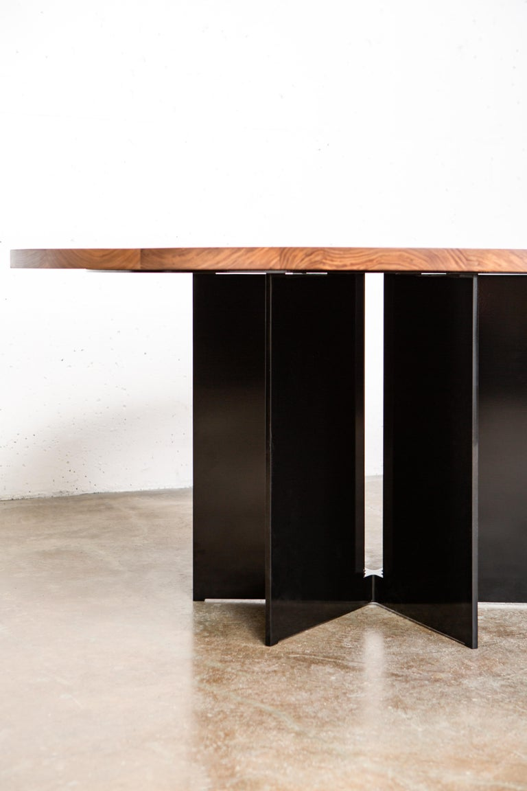 The Mers dining table  is fabricated from solid aluminum and is suitable for use indoors and out. Form is inspired by the simple utilitarianism of West Coast aluminum fishing boats.  Shown in aluminum with black powdercoat finish, black walnut