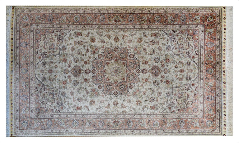 A mesmerizing vintage Egyptian silk Tabriz rug with a beautiful large central floral medallion with myriad flowers and leaves woven in crimson, indigo, yellow, pink, and white silk amidst a field of more flowers and vines against a white background.