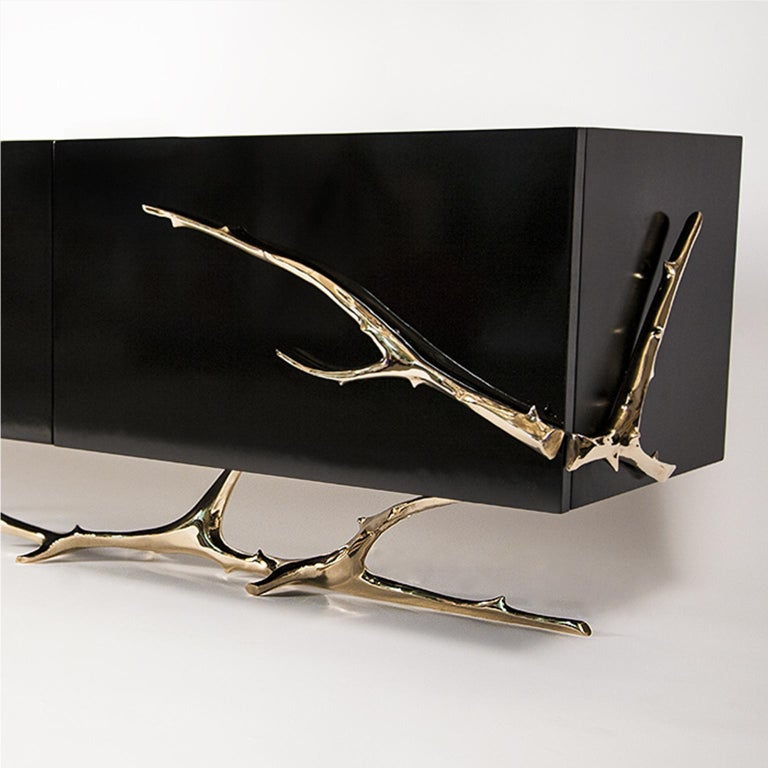Designed by Barlas Baylar, Meta Credenza reveals a refined sculptural aesthetic with its exquisitely handcrafted jewelry-like polished bronze base. High polished black-lacquered cabinet also complements its artistic silhouette.