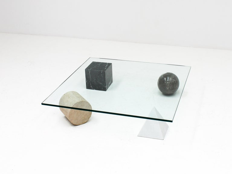 A 'Metafora' coffee table by Massimo and Lella Vignelli for Casigliani, Italy.   Constructed of four geometric marble shapes which form the base including a solid Carrara marble pyramid, travertine cylinder, black marble block and granite sphere and