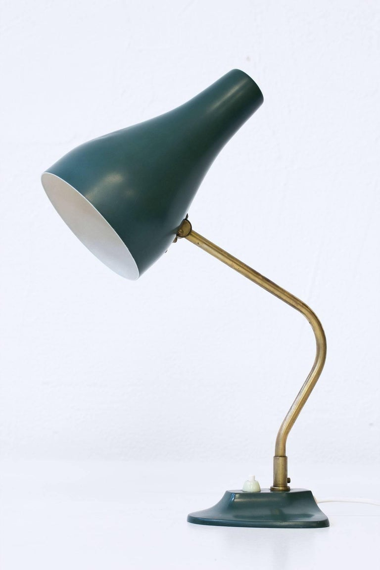 Swedish table lamp manufactured by ASEA during the 1950s.  Brass stem with diffuser and base in green painted metal.  Adjustable shade and axis. Signed on bottom.