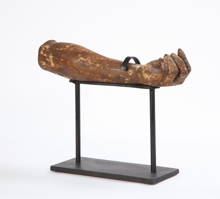 This is a sculptural fragment of a cast, patinated metal arm elevated on a black-painted metal stand. The lifelike metal arm fragment makes for a true conversation starter and would be an attractive centerpiece on a sideboard or hall table. Dating