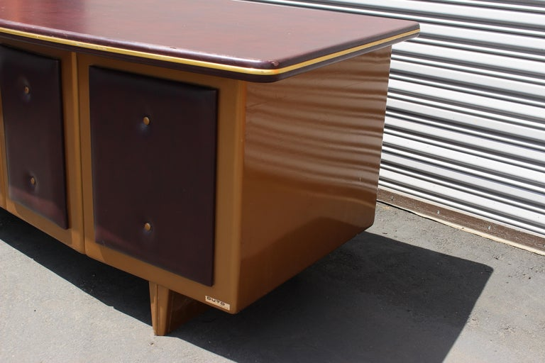 Italian metal desk, 1960s by Duto. Metal desk with the vinyl top and the some vinyl in the front .Antique gold color on the metal and the Burgundy vinyl on the front and top.