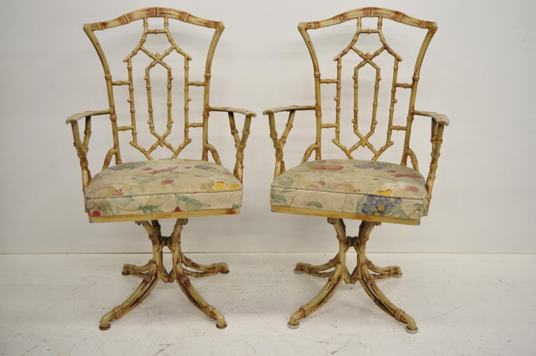 Vintage metal faux bamboo Hollywood Regency / Chinese Chippendale style five-piece dining set with swivel chairs. Listing features two armchairs, two side chairs, pedestal base table with round smoked glass top, swivel seats, yellow finish, great