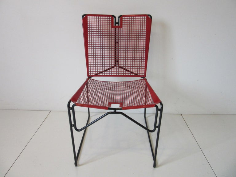 A pair of folded and perforated red and black metal chairs with sculptural rod frames and round ball details . Made in France in the manner of Mathieu Mategot .