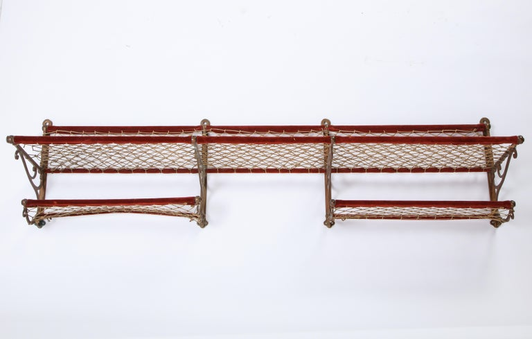 This large metal luggage rack with red plush trimming and netting probably dates to the early 20th century. Tracing its ties to a European train, this piece is both functional and decorative, adding a late Victorian flair to any room. Choose to add