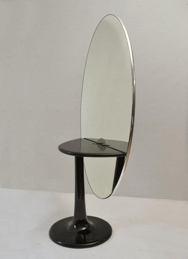 Extraordinary Mid-Century Modern sculptural oval table with black glass top trimmed with a chromed edge that stands off centre from its elliptical form tabletop on a black tulip foot. This table is metamorphic, it can be a dining table / desk when