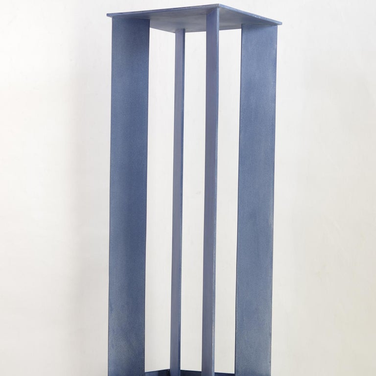 A tribute to Giorgio De Chirico, this iron sculpture is part of the Torri series (towers in English) and features a sturdy square base supporting an intriguing upright construction. The structure has four flat panels in the corners of the base