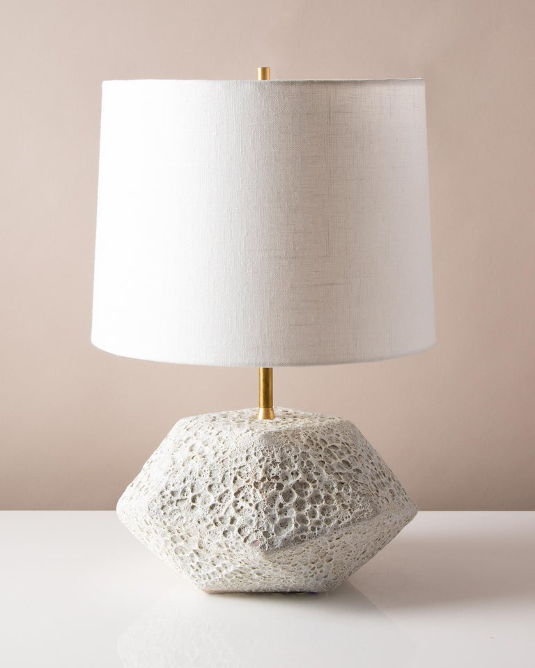 This dramatic white ceramic table lamp features a complex geometric shape, accentuated by a textured white glaze reminiscent of volcanic rock. Each piece is individually handmade and entirely unique. The lamp is finished with raw brass hardware and