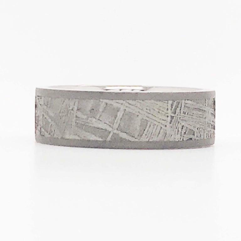 This custom titanium meteorite band ring is a durable, industrial, and unique design! The band is a flat band style titanium band with an inlay of a meteorite!  The band is 7 mm wide and made with a 5mm wide inlay of a genuine meteorite! The