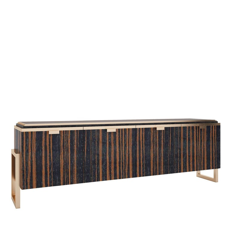Sustained by two square metal frames with a bright brass finish, this exclusive wooden sideboard boasts four vertically carved doors and a dark brown-lacquered top embellished with a brass-finished metal frame. The same brass finish adorns the front