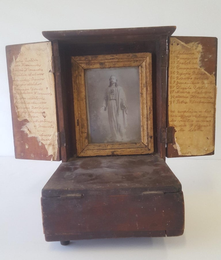 A small wooden altar with a framed guilt framed print of Christ used for personal devotion and an interior locked coin box for offerings.