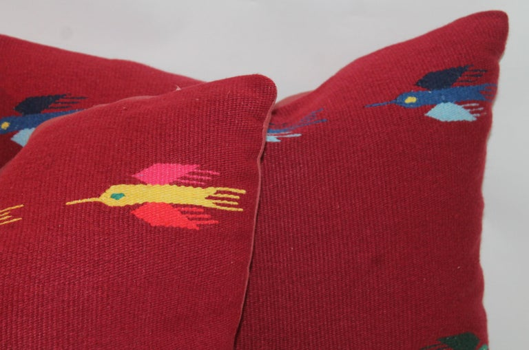 These cool Indian weaving pillows in the birds in flight pattern. The backing is in a cranberry cotton linen. All the colors in the Mexican serapes. Fantastic graphics. Two pairs in stock.