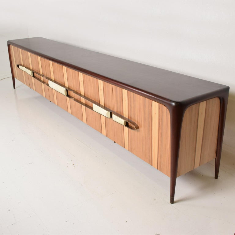 For your consideration, a Mexican modernist long credenza attributed to Eugenio Escudero. Mahogany wood frame, with brass and goatskin pull handles. The doors have red gum veneer with maple in the inside.  Restored.  Mexico, circa