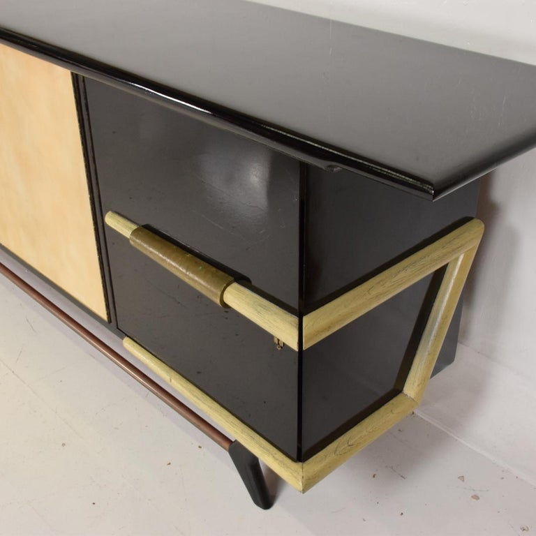 For your consideration a beautiful credenza made in mahogany with a custom finish (black glossy lacquer).  Attributed to Eugenio Escudero. Center doors are covered with goatskin. Beautiful brass accents with original patina.   Parchment doors