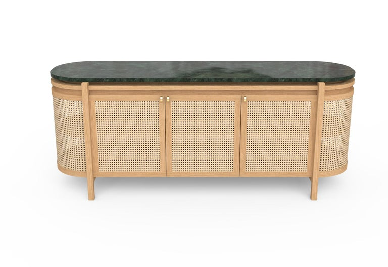 This sideboard gives an elegant accent to any dining room. A Guatemalan green Tikal marble top floats above a handwoven body, in contrast to its sturdy wooden structure.  The body is woven in natural wicker allowing for a sense of spaciousness and
